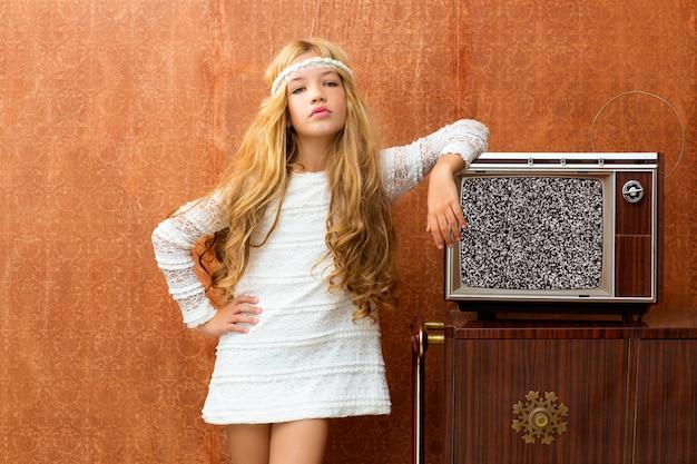 Fille d'enfant blonde vintage des années 70 avec télévision en bois rétro
