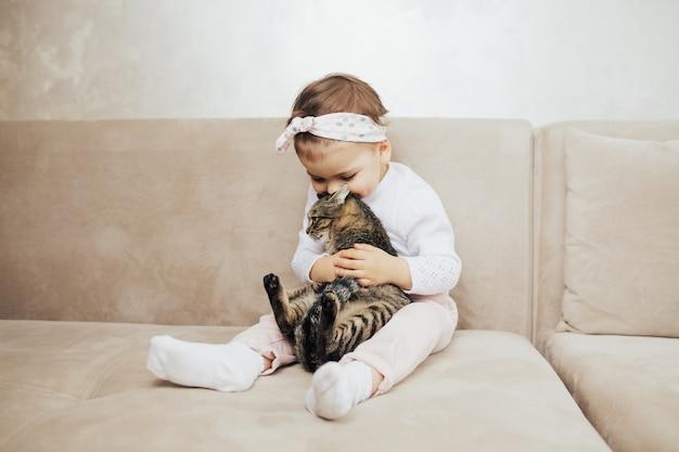 Fille enfant câlin et embrasse son chat drôle mignon avec tendresse et amour