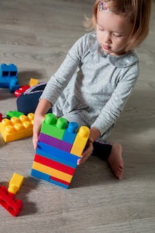 Fille enfant construire des blocs de construction en plastique brillant