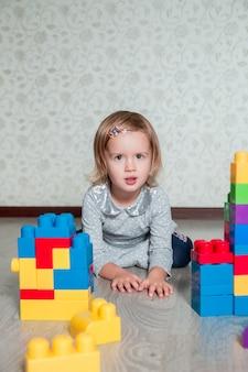 Fille enfant couchée près de blocs de construction en plastique brillant. tout-petit jouant sur le sol. développer des jouets. apprentissage précoce.