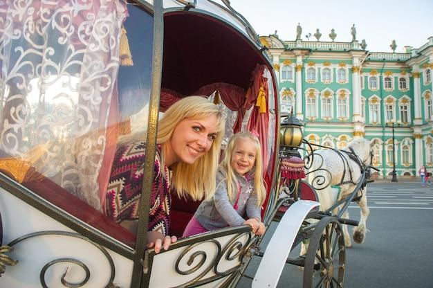 Une fille avec un enfant dans une vieille voiture sur la place du palais à saint-pétersbourg