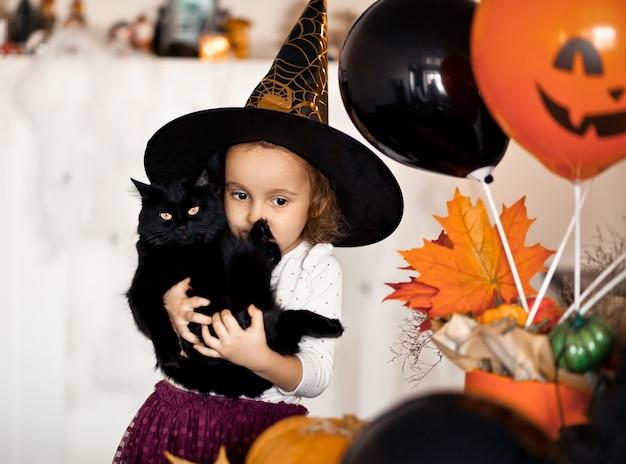 Fille enfant drôle en costume de sorcière pour halloween avec chat noir dans les mains.