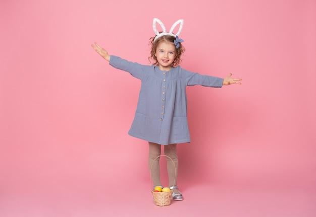 Fille enfant drôle dans les oreilles de lapin de pâques tenant un panier avec des oeufs colorés.