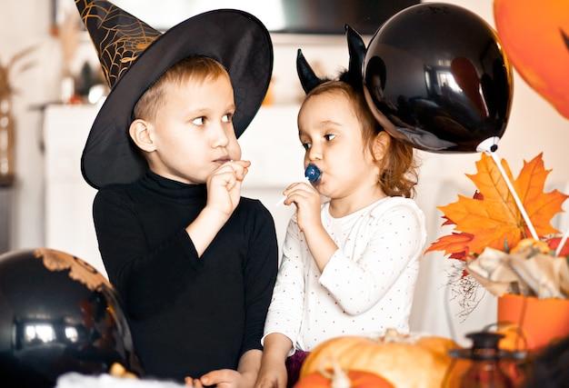 Fille enfant drôle et garçon adolescent en costumes de sorcière et de mal pour la fête d'halloween, manger des bonbons et s'amuser