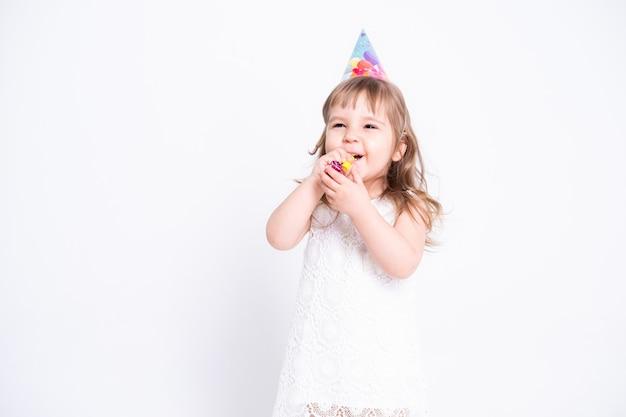Fille enfant drôle en robe blanche et chapeau d'anniversaire soufflant dans le sifflet sur le mur blanc