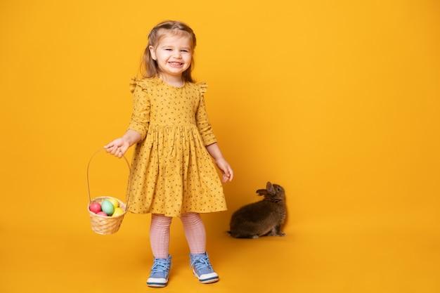 Fille enfant drôle en robe jaune avec lapin tenant panier avec des oeufs colorés sur fond jaune.