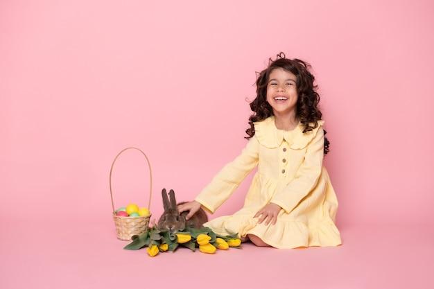 Fille enfant drôle en robe jaune avec lapin, tulipes, panier avec des oeufs colorés