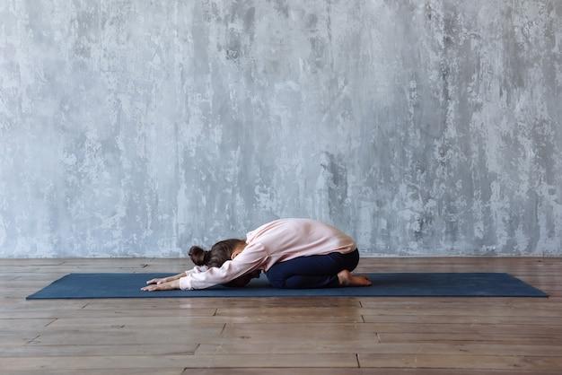 Fille enfant faisant du yoga sur tapis pratiquant une pose relaxante