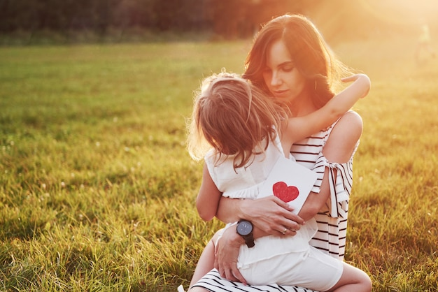 La fille de l'enfant félicite sa mère et lui donne une carte postale.