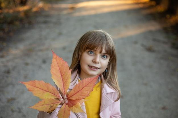 Fille enfant heureuse avec des feuilles d'automne à l'extérieur.