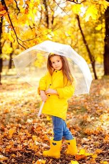 Fille enfant heureuse avec un parapluie et des bottes en caoutchouc une promenade d'automne
