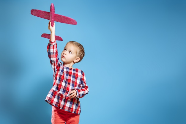 Fille enfant heureux jouant avec un avion jouet. le rêve de devenir pilote.