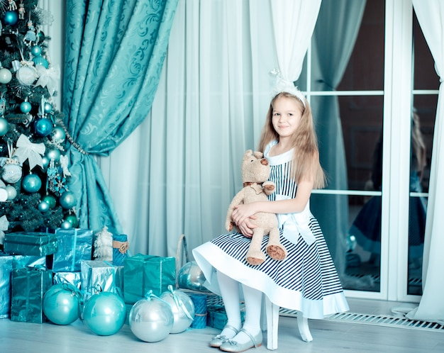 Fille enfant heureux avec jouet dans la salle de décoration de noël. tonique