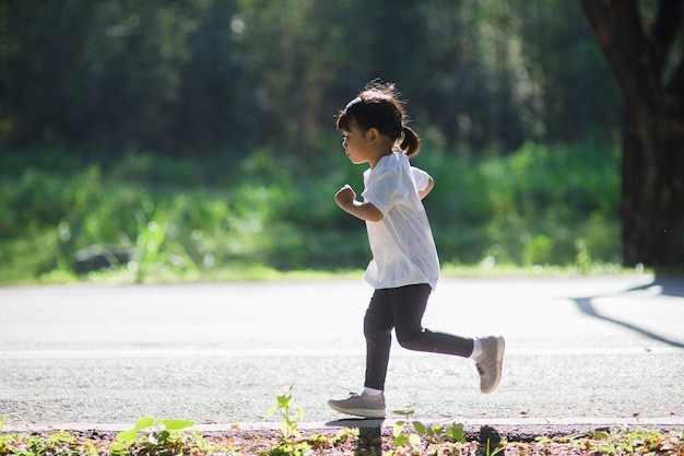 Fille enfant heureux qui court dans le parc en été dans la nature. lumière chaude du soleil. petit asiatique court dans un parc. sports de plein air et fitness, apprentissage de l'exercice et de la compétition pour le développement des enfants.