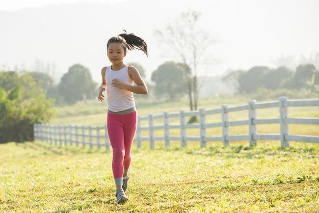 Fille enfant heureux qui court sur le pré en été dans la nature. lumière chaude du soleil. petit asiatique court dans un parc. sports de plein air et fitness, apprentissage de l'exercice et de la compétition pour le développement des enfants.
