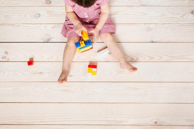Fille enfant jouant au lego sur un plancher en bois clair.