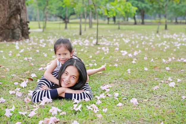 Fille enfant joyeuse câliner sa mère allongée sur un champ vert.