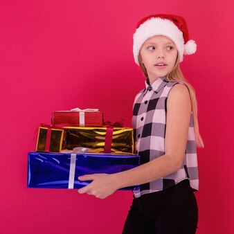 Fille enfant joyeuse souriante drôle en bonnet de noel tenant un cadeau de noël à la main sur fond rouge