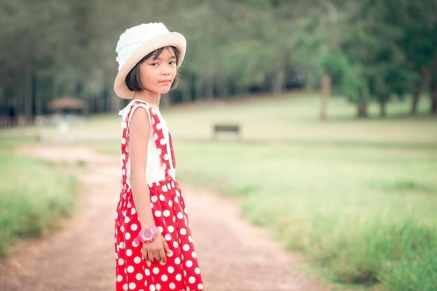 Fille d'enfant marchant et jouant dans la prairie pendant la journée
