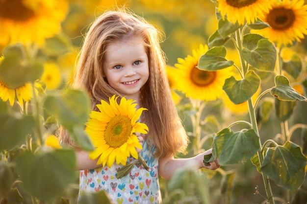 Fille enfant mignon dans le jardin jaune de tournesols