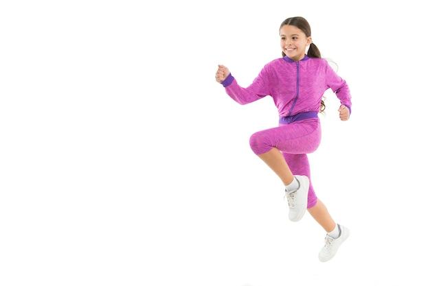 Fille enfant mignon avec de longues queues de cheval costume sportif saut isolé sur blanc. travailler avec les cheveux longs. sport pour les filles. conseils pour travailler avec les cheveux longs. traitez les cheveux longs pendant l'exercice.