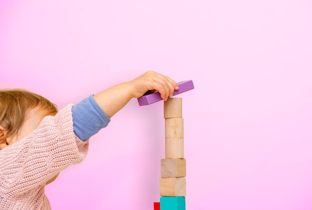 Fille enfant mignonne et charmante à la maison, jouant avec des jouets de blocs de construction en bois.