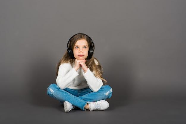 Fille enfant mignonne dans les écouteurs appréciant la musique de danse heureuse, sourire, posant sur le mur de fond gris studio.
