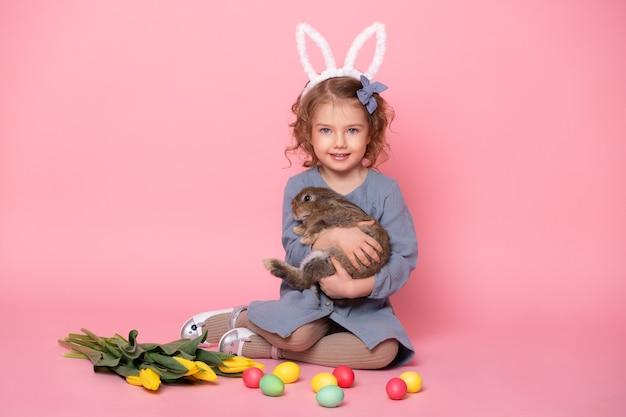Fille enfant mignonne dans les oreilles de lapin tenant lapin, tulipes, oeufs colorés.