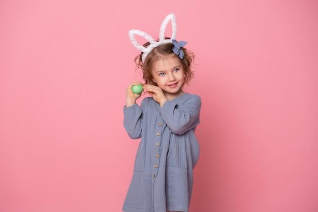 Fille enfant mignonne drôle dans les oreilles de lapin de pâques et robe blu tenant des oeufs colorés.