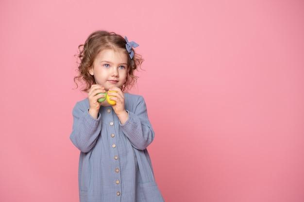 Fille enfant mignonne drôle en robe blu tenant des oeufs colorés de pâques.