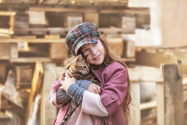 Fille enfant à la mode belle et heureuse avec un mignon petit chaton bengal ensemble dans la rue