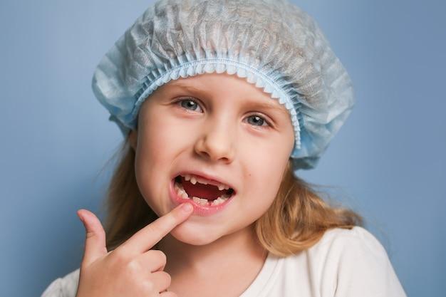 Fille enfant montre le médecin avec son doigt sur les dents de lait tombées.