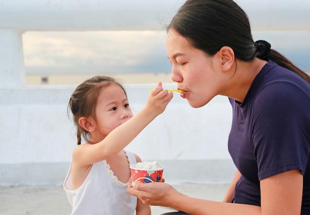 Fille enfant nourrissant la crème glacée à sa mère