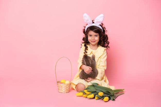 Fille enfant en oreilles de lapin tenant lapin, tulipes, panier avec des oeufs colorés.