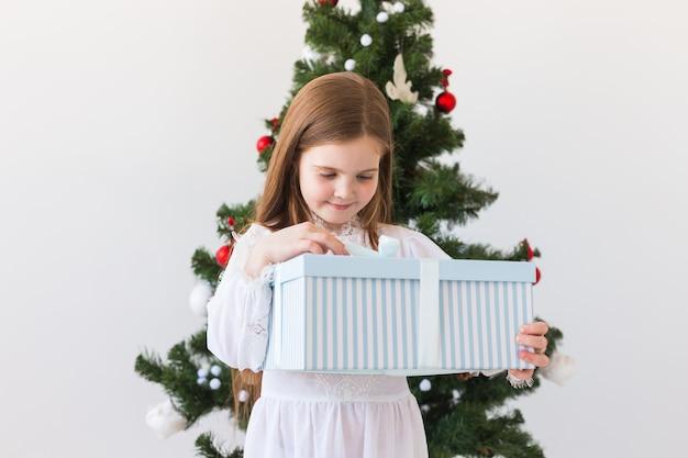 Fille enfant ouvre la boîte-cadeau près de l'arbre de noël