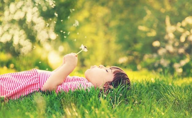 Fille enfant avec des pissenlits dans le parc