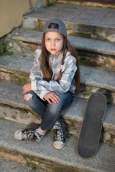 Fille enfant avec planche à roulettes assis sur des escaliers en béton