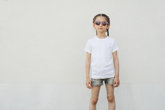 Fille enfant portant un t-shirt blanc avec un espace pour votre logo ou design dans un style urbain décontracté