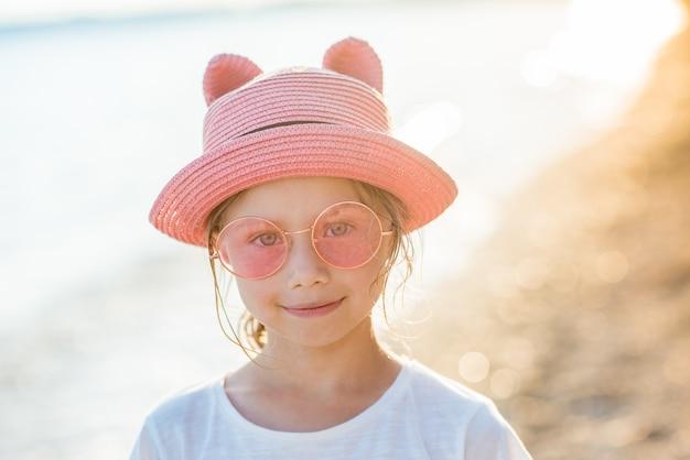 Fille enfant souriante au chapeau rose et lunettes de soleil sur la côte de l'océan