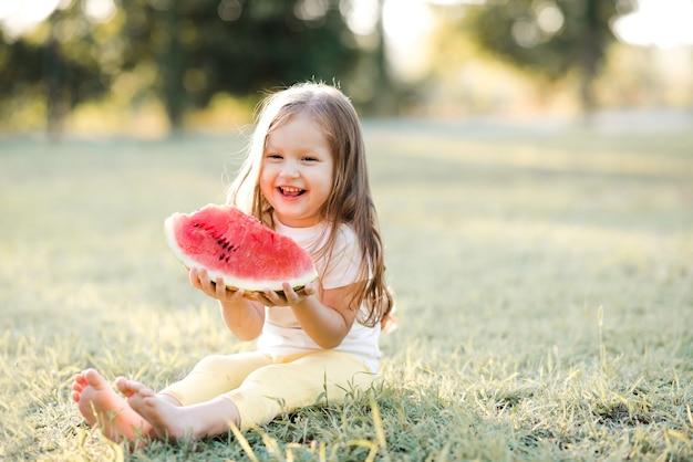 Fille d'enfant de sourire mangeant la pastèque mûre