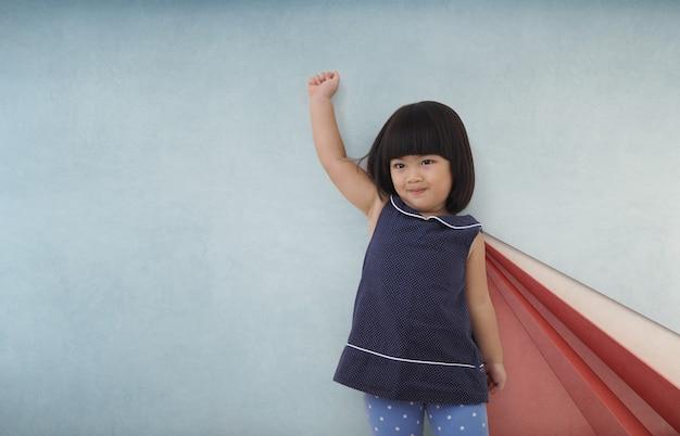 Fille enfant super-héros asiatique jouant.