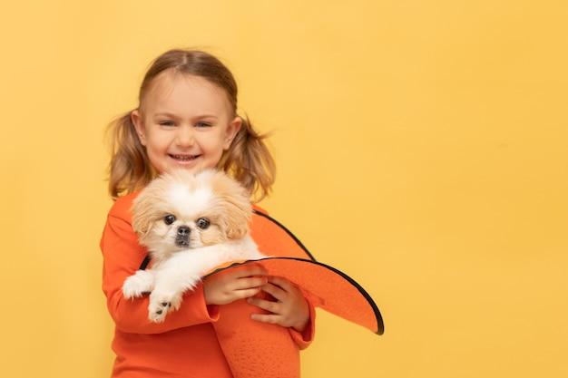 Fille enfant tenir chiot dans un chapeau d'halloween fond de studio jaune isolé halloween party focus chien