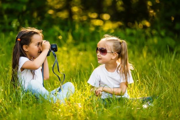 Fille d'enfants assis dans l'herbe avec un appareil photo