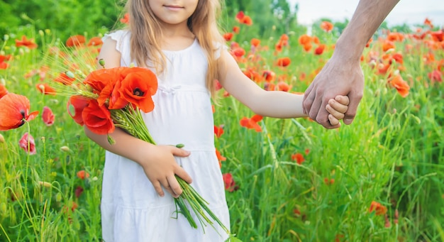Fille d'enfants dans un champ avec des coquelicots.