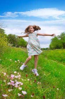 Fille d'enfants heureux sautant sur les fleurs de pavot de printemps