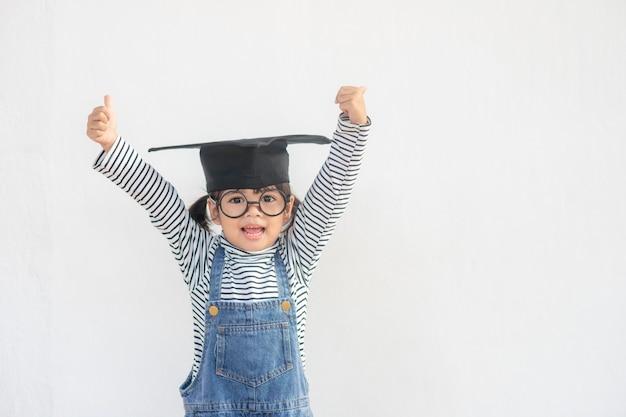 Fille d'enfants portant une casquette de diplômé sur fond blanc très heureuse et excitée en faisant le geste du gagnant avec les bras levés, souriant et criant pour le succès. notion de célébration.
