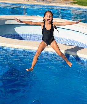 Fille d'enfants sautant au maillot de bain noir bleu piscine