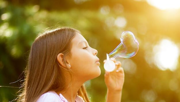 Fille d'enfants soufflant des bulles de savon en plein air