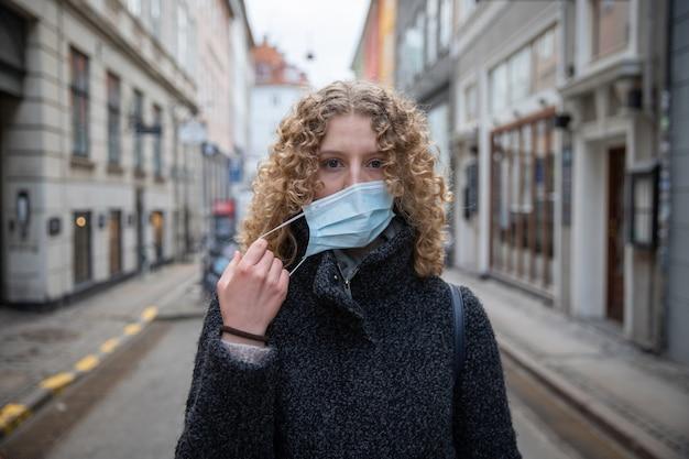 Une fille enlève le masque chirurgical qu'elle utilise pour se protéger de la pandémie de coronavirus.