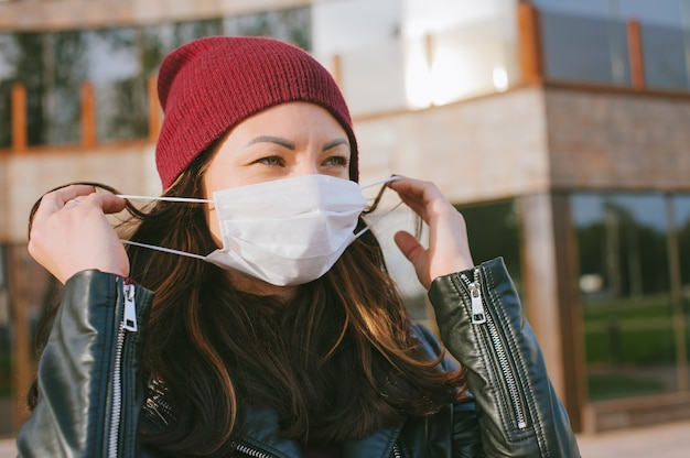 La fille enlève le masque médical de son visage. dans le contexte d'un centre d'affaires en verre.